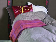 Bed with checkered bed linen and bedspread
