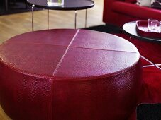 Red leather ottoman in front of side tables