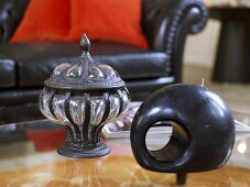 Antique container made of metal and glass and wooden sculpture in front of a sofa