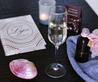 Stemware glass next to a rose colored shell with items for the bathroom on a black counter