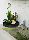 Stone sink in front of white tiles with a black tray and flowers