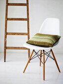 Bauhaus chair with striped pillow in front of a wooden ladder