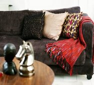 Brown corduroy sofa with pillows and a red throw