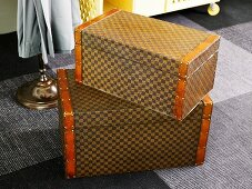 Brown luggage set with a checkerboard design on a carpet
