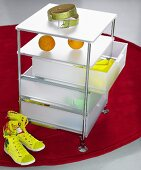Rolling cabinet with plastic drawers and sneakers on a red carpet