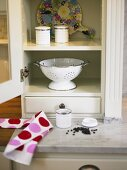 A white crockery cupboard with an open door and an old enamel colander inside