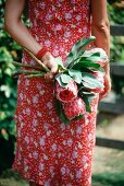 A woman holding a bunch of protea flowers behind her back