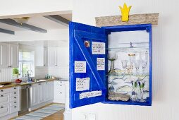 Glasses in an open wall cupboard and view into a white country house kitchen