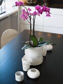 Pink orchids in a white pot and various tea light holders on the table