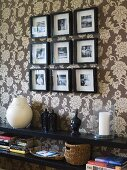 A black shelf and black-framed pictures on a wall hung with floral wallpaper