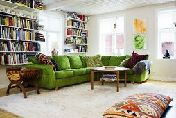 A corner of a living room with a green sofa and a book shelf next to a window