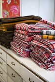 A stack of patterned blankets on a white, vintage chest of drawers