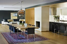 A dining room in an open-plan living room-cum-dining room with black walls and designer furniture