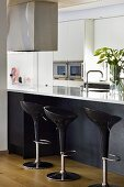 Black plastic bar stools in front of a kitchen counter with a white work surface