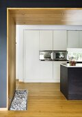 A view into an open-plan kitchen with a wooden wall and ceiling and a white fitted cupboard