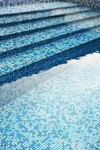 Blue mosaic tiles on stone steps leading to a pool filled with water