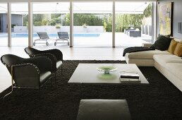 A living room room with a large window - black leather armchairs and a coffee table on a black rug with a view of the terrace