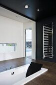 Black and white designer bathroom with sunken bathtub and towel warmer on a black wall
