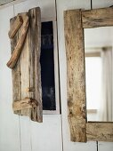 A homemade wooden door for a built-in cupboard and a mirror on a wall