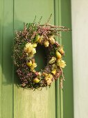 A wreath of dried flowers and fruits on a wooden green door