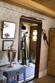 A wooden country house - a samovar on a wall table, a view through a doorway onto front door