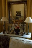 Table lamps on the top of a marble table and a mirror with a gold frame