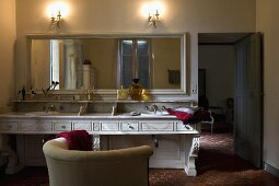 Country style bathroom -- ambient wall lighting above a long vanity with a mirror