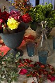 An arrangement of roses in an antique metal vase, flower pot and a decanter