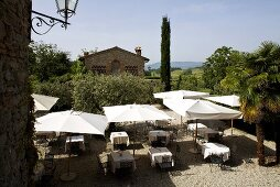 Restaurant terrace with dining areas under sun umbrellas with a view of a Mediterranean countryside