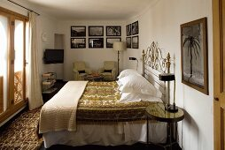 Bedroom with a double bed and seating corner with a collection of pictures