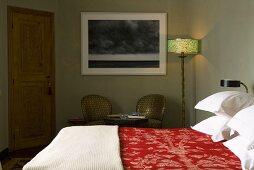 Half-darkened bedroom with double bed and floor lamp