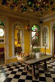Colourful metal balls hanging from the ceiling in an oriental dining room with a table on a chessboard patterned floor