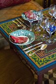 A place setting with wine glasses on an Oriental table