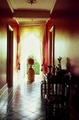 Elegant hallway with red walls, floor to ceiling window with the curtains drawn back