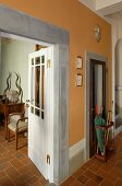 Hallway with orange walls and doorway framed with stone, open door with a view into a living room
