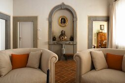 Armchairs upholstered in light gray and busts in a wall niche framed with stone