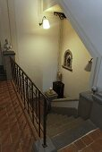 View of a stairway with ambient wall lighting and terracotta flooring in an elegant country home