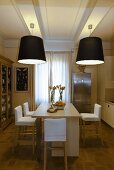 Dining room with black lampshades hanging from the ceiling and a kitchen counter with bar stools