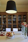 Black lampshades above a dining table with flower vases and a fruit bowl in front of a glass front cabinet
