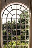 View through an arched window of a garden