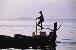 Sunrise with a fishing boat on the sea -- a fisherman serenely steers a full boat