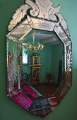 Decorated mirror on a green wall with a reflection