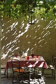 Refreshing drinks on a table in a courtyard with a high stone wall