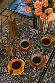 'Coffee break oriental style' -- colorful coffee cups with coffee on a glass table
