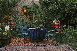 Romantic picnic -- blue patio furniture on a oriental rug with lanterns and tea lights