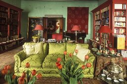 Living room with a green sofa and mahogany bookcases in front of a green wall