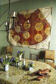 Dining room with oriental flair -- table with floral decorations and picture on a green wall