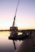 Abendstimmung über Fluss mit Boot und Takelage am Ufer, Nil, Ägypten