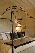 A canopy bed frame made of curved metal in a country style bedroom