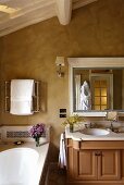 Country style bathroom beneath the roof with a vanity and mirror in front of a marbled yellow wall